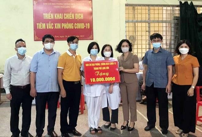 Đồng chí Nông Bích Diệp (thứ 3 từ phải sang), Phó Bí thư Thường trực Thành uỷ cùng đoàn công tác thăm, trao tặng 10 triệu đồng tại điểm tiêm phường Hoàng Văn Thụ, thành phố Lạng Sơn
